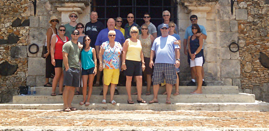 The Lynette Owens Advisory Council posed for a group shot in front of the Church of St. Stanislaus in Altos de Chavón, a replica of a 16th century Mediterranean village in the resort area of La Romana, Dominican Republic. Credit: Lynette Owens & Associates