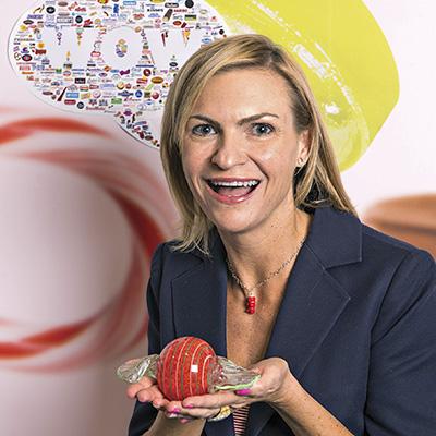 Jenn Ellek, Senior Director, Trade Marketing & Communications, National Confectioners Association holds candy glass art.