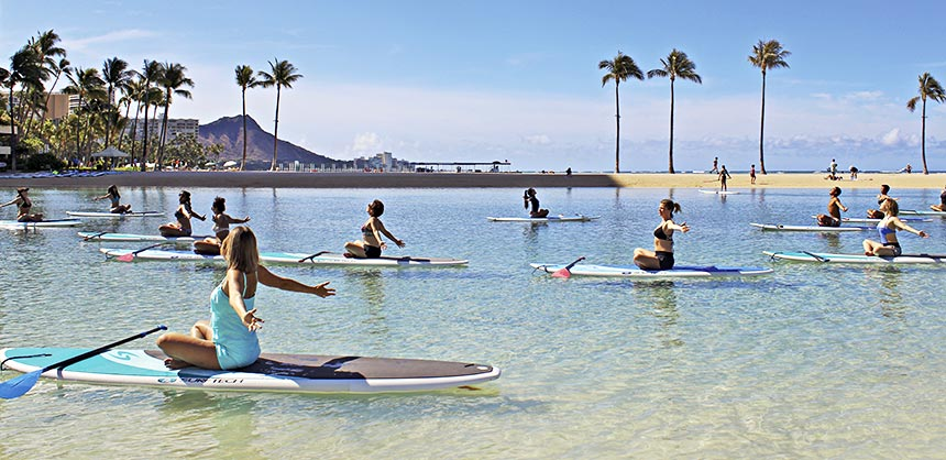 Group yoga on standup paddleboards at Hilton Hawaiian Village Waikiki Beach Resort.