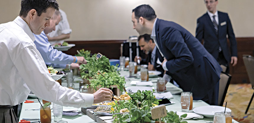 "Attendees gather around a conference table to assemble a ""Cut & Create Salad"" with local greens and more."