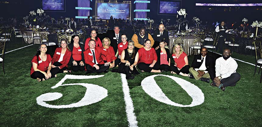 Aflac's Heidi Carlisle (c) and her team on the 50-yard line at the Mercedes-Benz Superdome. Credits: Aflac