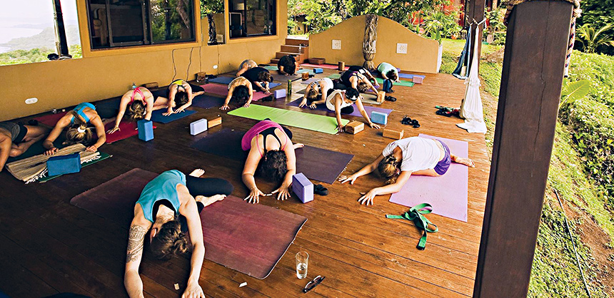 COURTESY OF KSENIJA SAVIC At a Women's Wellness Retreat at Anamaya Resort in Costa Rica, attendees relax by doing yoga on the deck at the center.