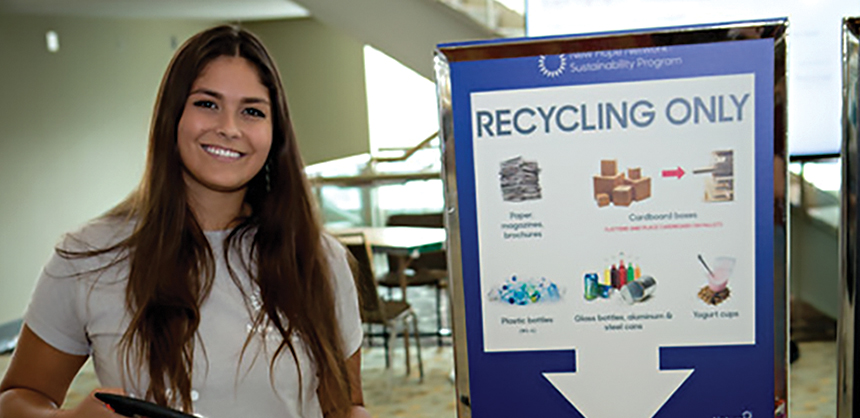 A volunteer at an event encourages attendees to recycle. Planners say some clients may be reluctant to change, so they suggest bringing clients along slowly to ease the transition. (Courtesy of Lindsay Arell)