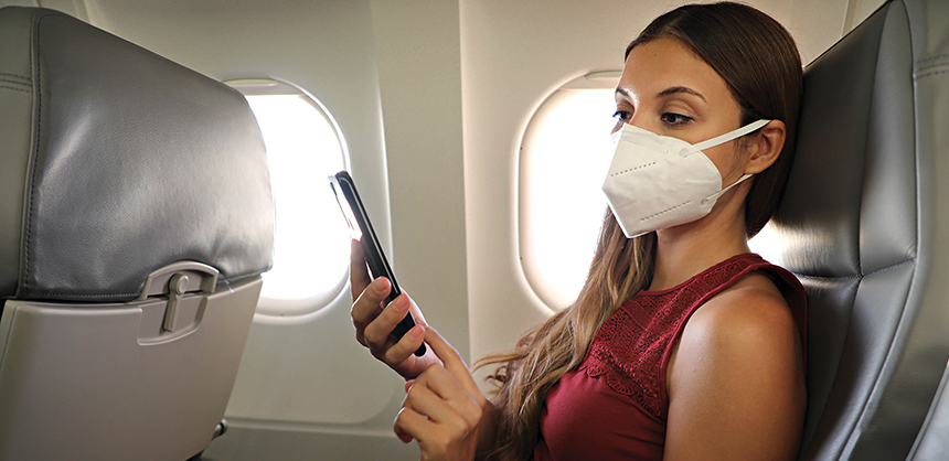 COVID-19 Young woman on airplane wearing KN95 FFP2 protective mask reading information on mobile phone during coronavirus pandemic